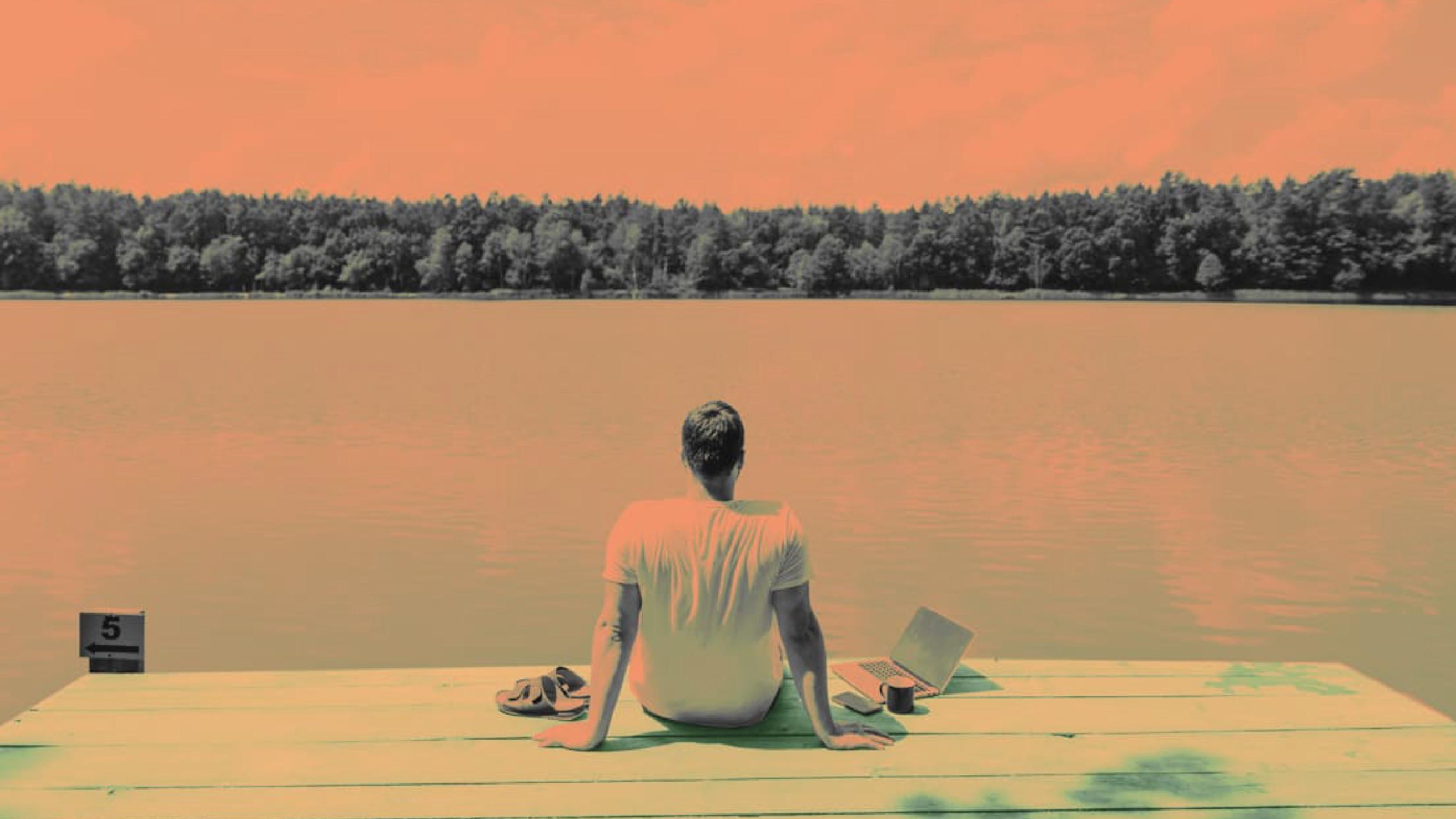 Man sitting on a dock facing a lake